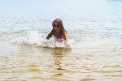 Glückliches kleines Mädchen, das in den Wellen des seichten Wassers spielt lizenzfreie stockfotos