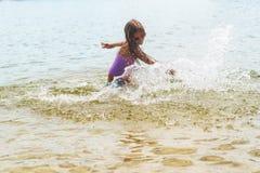 Glückliches kleines Mädchen, das in den Wellen des seichten Wassers spielt Glückliches kleines Mädchen stockfotografie