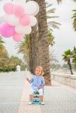 Glückliches kleines Mädchen, das ein Bündel Ballone hält Lizenzfreie Stockfotos
