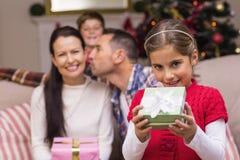 Glückliches kleines Mädchen, das ein Geschenk öffnet Stockfotografie