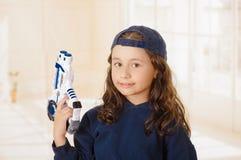 Glückliches kleines Mädchen, das ein Gewehr in ihren Händen hält und Jungenkleidung trägt stockfoto