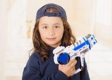 Glückliches kleines Mädchen, das ein Gewehr in ihren Händen hält und Jungenkleidung trägt stockbild