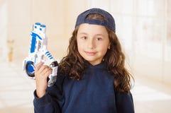 Glückliches kleines Mädchen, das ein Gewehr in ihren Händen hält und Jungenkleidung trägt stockfotografie