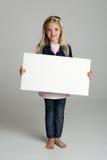 Glückliches kleines Mädchen, das ein unbelegtes Zeichen anhält Lizenzfreie Stockbilder