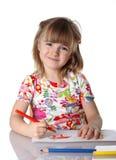 Glückliches kleines Mädchen, das eine Abbildung zeichnet Stockbild