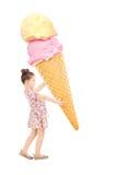 Glückliches kleines Mädchen, das eine enorme Eiscreme hält Lizenzfreies Stockbild