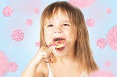 Glückliches kleines Mädchen, das eine Lutschersüßigkeit isst Lizenzfreie Stockfotografie