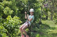 Glückliches kleines Mädchen, das eine Ziplinie in einem üppigen tropischen Wald reitet Stockfoto