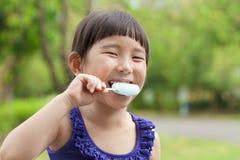 Glückliches kleines Mädchen, das Eis am Stiel an der Sommerzeit isst Stockfotos