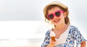 Glückliches kleines Mädchen, das Eiscreme auf Strand isst Lizenzfreie Stockfotografie