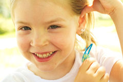 Glückliches kleines Mädchen, das Haarspange hält stockfoto