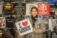Glückliches kleines Mädchen, das Hemd mit London-Zeichen hält Stockbilder