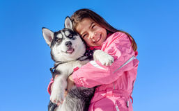 Glückliches kleines Mädchen, das ihr Hündchen heiser hält Stockbild