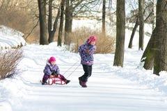 Glückliches kleines Mädchen, das ihre junge Schwester auf den Schlitten im Park des verschneiten Winters zieht Stockfotografie