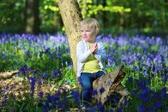 Glückliches kleines Mädchen, das im Glockenblumewald spielt Stockfotografie