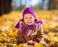Glückliches kleines Mädchen, das im Herbstpark spielt Stockbilder