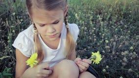 Glückliches kleines Mädchen, das im Park sitzt stock footage