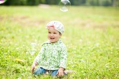 Glückliches kleines Mädchen, das im Park spielt Stockbild