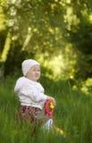 Glückliches kleines Mädchen, das im Sommer sitzt Stockbild