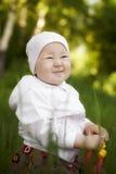 Glückliches kleines Mädchen, das im Sommer sitzt Stockfotos