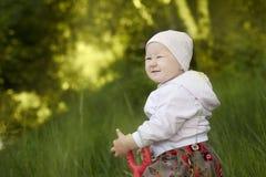 Glückliches kleines Mädchen, das im Sommer sitzt Stockfoto