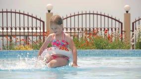 Glückliches kleines Mädchen, das mit buntem aufblasbarem Ring Swimmingpool im im Freien am heißen Sommertag spielt Kinder lernen  stock video