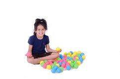 Glückliches kleines Mädchen, das mit bunten Bällen spielt stockfotografie