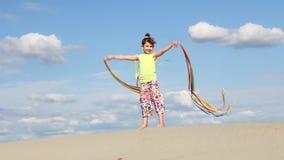 Glückliches kleines Mädchen, das mit bunten Bändern wellenartig bewegt Lizenzfreie Stockbilder