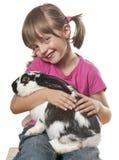 Glückliches kleines Mädchen, das mit ihrem Kaninchen spielt Stockbild