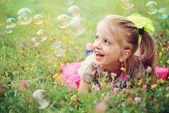 Glückliches kleines Mädchen, das mit Luftblasen spielt stockbild