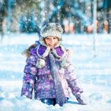 Glückliches kleines Mädchen, das mit Schnee spielt Lizenzfreies Stockbild