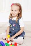 Glückliches kleines Mädchen, das mit Spielwaren spielt Stockbild
