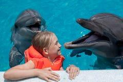 Glückliches kleines Mädchen, das mit zwei Delphinen im Swimmingpool lacht Stockbild