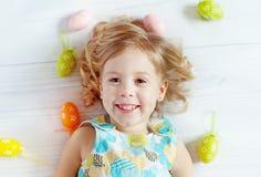 Glückliches kleines Mädchen, das Ostereier hält Stockfoto