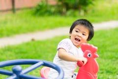 Glückliches kleines Mädchen, das rotes Huhn am Spielplatz reitet stockbilder
