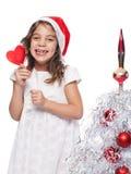 Glückliches kleines Mädchen, das Sankt-Hut mit Lutscher trägt Stockfoto