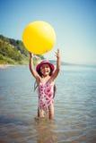 Glückliches kleines Mädchen, das sonnigen Tag am Strand genießt Spiele mit einem großen gelben Ball Lizenzfreies Stockfoto