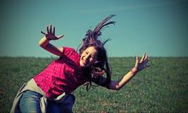 Glückliches kleines Mädchen, das Spaß auf einer Wiese mit Filtertonne habend springt Stockbild