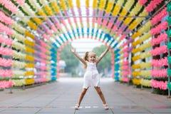 Glückliches kleines Mädchen, das Spaß auf unscharfer heller sonniger Parkgasse springt und hat Gl?ckliches unvorsichtiges Kindhei lizenzfreies stockfoto