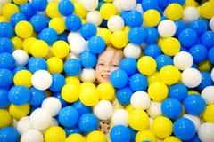Glückliches kleines Mädchen, das Spaß in der Ballgrube in Kinderder innenspielmitte hat Kind, das mit bunten Bällen im Spielplatz Stockfoto