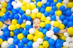 Glückliches kleines Mädchen, das Spaß in der Ballgrube in Kinderder innenspielmitte hat Kind, das mit bunten Bällen im Spielplatz Lizenzfreies Stockfoto
