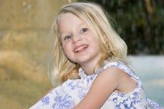 Glückliches kleines Mädchen, das vor einem Wasserbrunnen sitzt Stockfotos