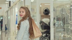 Glückliches kleines Mädchen, das zur Kamera, Einkaufstasche im Einkaufszentrum halten lächelt stock video footage