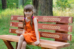 Glückliches kleines Mädchen in der Orange sitzt auf hölzernem beanch am Sommer Stockbild