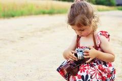 Glückliches kleines Mädchen in der Retro- Ausstattung, die Fotos mit altem Film macht Lizenzfreies Stockfoto
