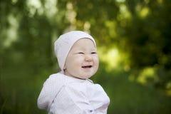 Glückliches kleines Mädchen in einem Kappenlachen Lizenzfreie Stockfotos