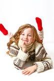 Glückliches kleines Mädchen in einer Strickjacke, die auf einem weißen Hintergrund liegt stockbild