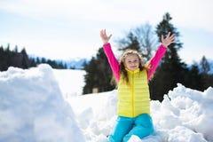 Glückliches kleines Mädchen hat Spaß witn Schnee draußen Stockfoto