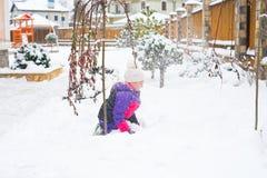 Glückliches kleines Mädchen im bunten Anzug und weißer Hut spielen mit Schnee stockfotos