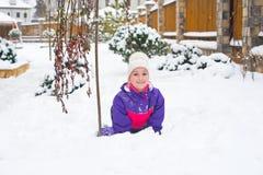 Glückliches kleines Mädchen im bunten Anzug und weißer Hut spielen mit Schnee stockbild